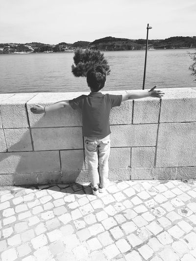 Rear view of boy standing on retaining wall against sea