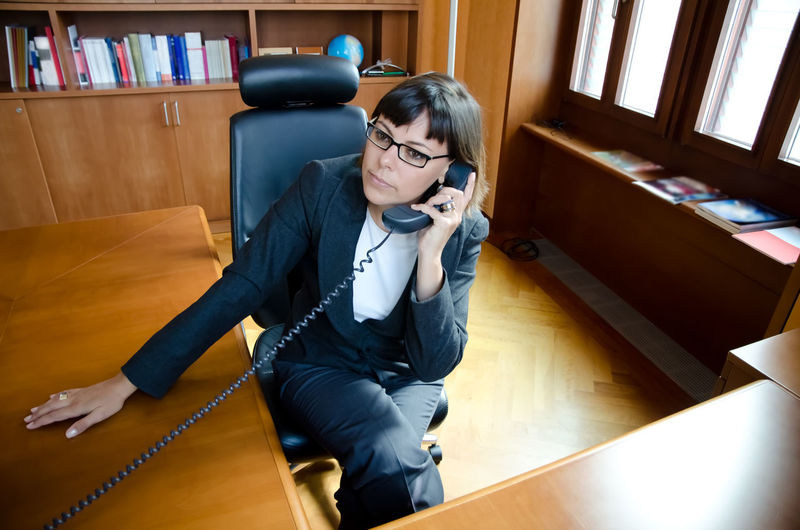Businesswoman holding phone while sitting on chair in office