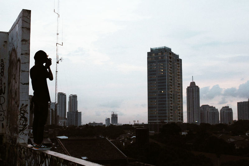 Silhouette man photographing buildings in city against sky