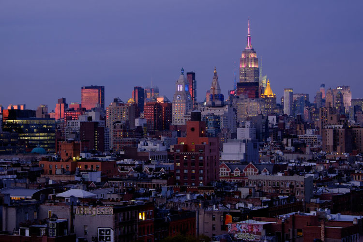 Illuminated empire state building in city against sky at dusk