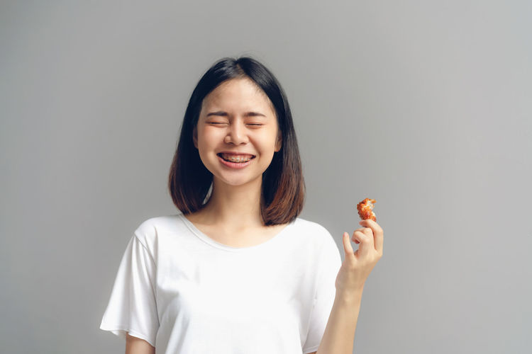 Happy woman holding fried chicken for eat. Front View Studio Shot One Person Smiling Happiness Indoors  Casual Clothing Portrait Emotion Waist Up Gray Hairstyle Gray Background Hair Teeth Standing Toothy Smile Holding