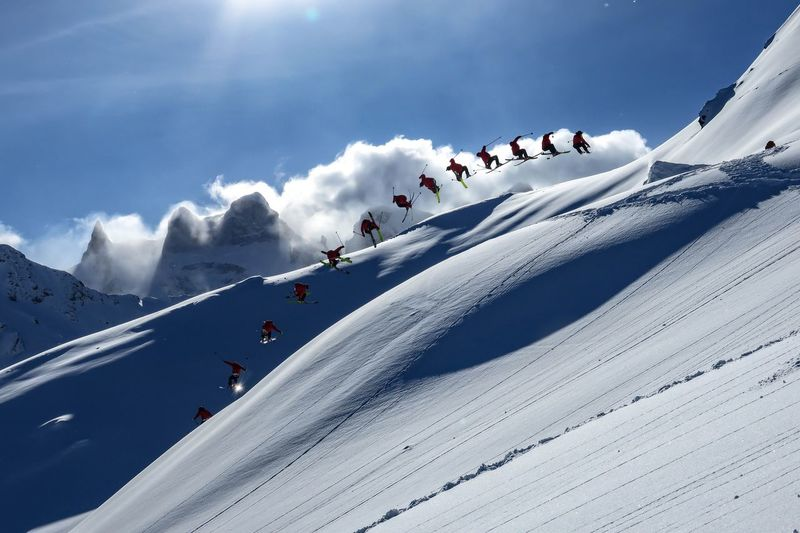 Multiple image of man skiing on snowcapped mountain against sky