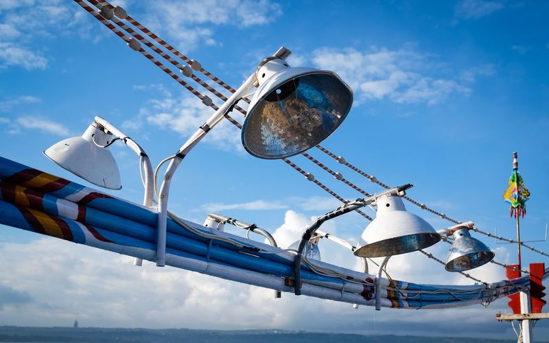 Lamps mounted on boat against sky