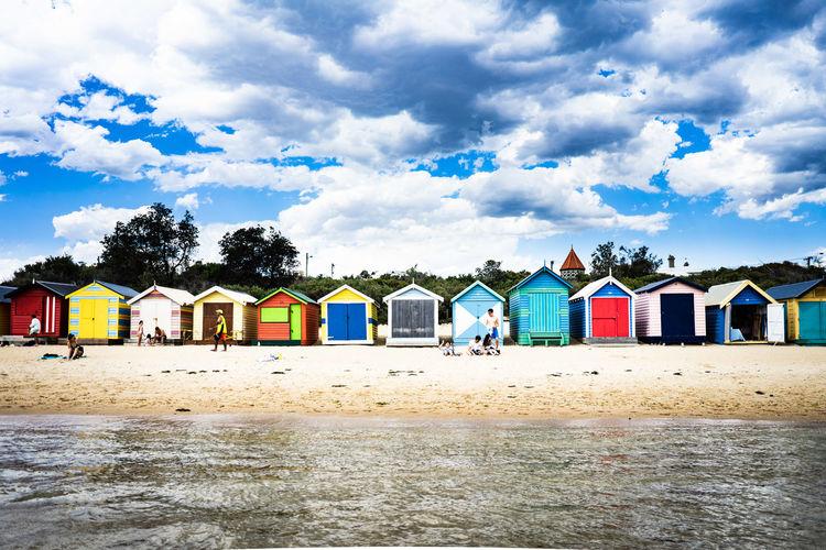 Beach huts by buildings against sky