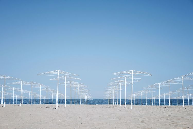 Empty parasols on beach against clear blue sky