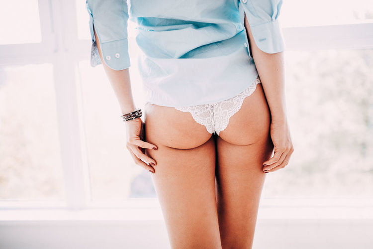 Midsection Of Sensuous Woman Wearing Panties By Window At Home