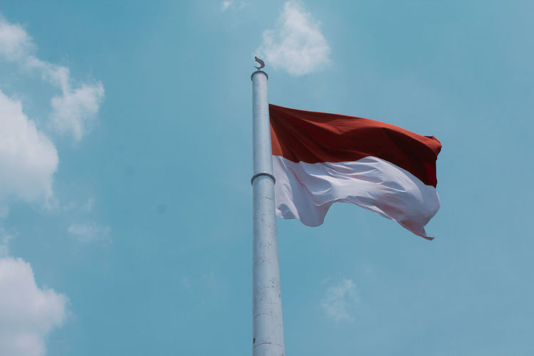 Waving flag of Indonesia Flying Blue Red Flag City Wind Sky Cloud - Sky Pole Electric Pole National Icon Skyscraper Tower National Flag Flag Pole Waving Symbolism Patriotism Tall - High Fluttering Urban Skyline First Eyeem Photo