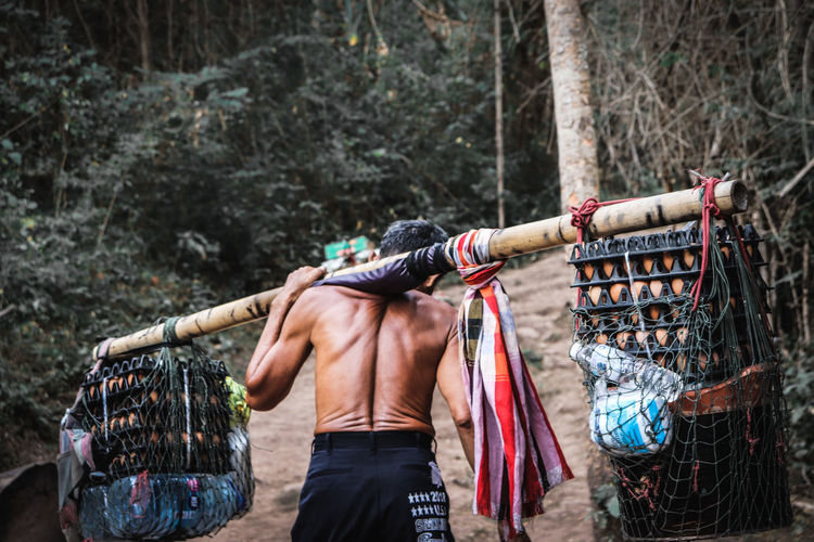 Rear view of man standing on clothesline