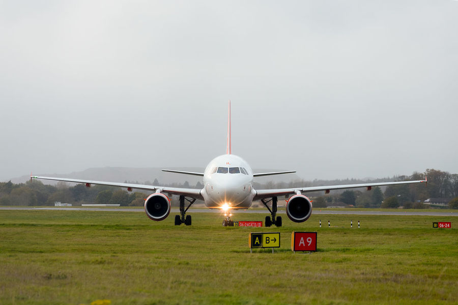 EasyJet passenger airplane G-EZIL Airbus A319-111 taxiing after landing at Edinburgh International Airport. Airbus Airbus A319 Airbus A319-111 Edinburgh Airport Grass Runway Airplane Airport Runway Day EasyJet Grass No People Outdoors Runway Signs Sky Taxiing Transportation