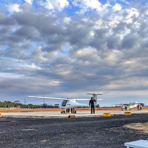 People at airport runway against sky
