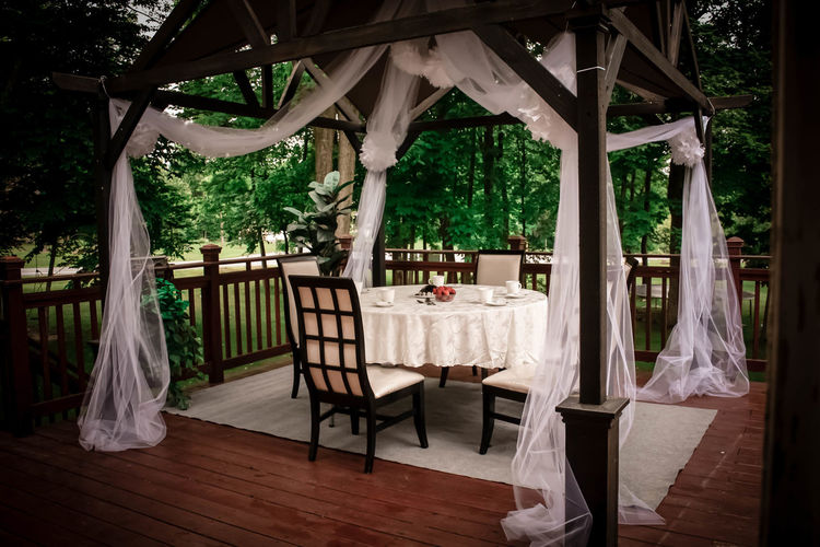 Empty chairs and tables in restaurant by garden