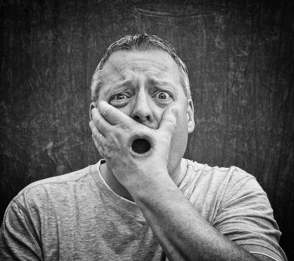 Digital composite image of shocked man with mouth seen through hand
