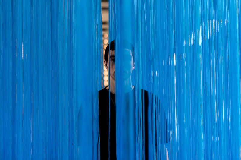 Portrait of man standing behind blue textile