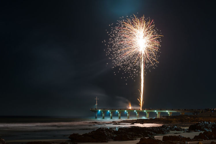 Firework display over sea against sky at night