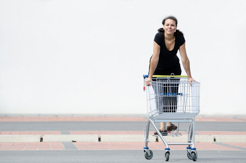 Full Length Portrait Of Smiling Woman Standing On Shopping Cart