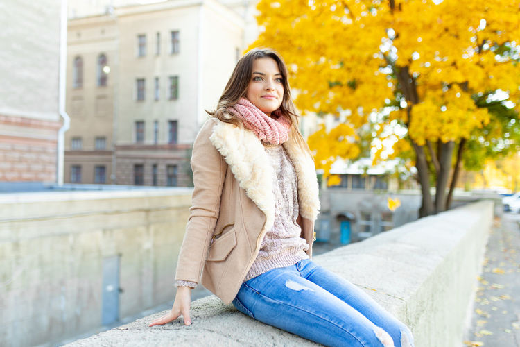 Woman sitting on wall in city during autumn