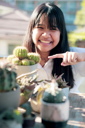 Portrait of smiling girl by potted plant outdoors