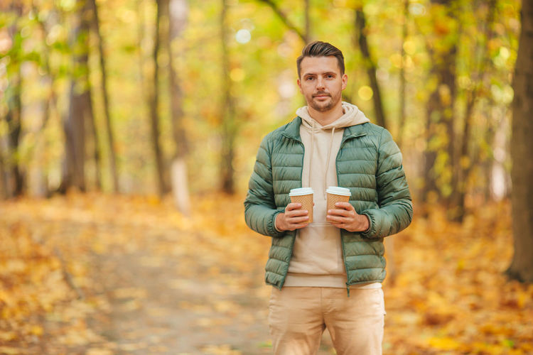 Portrait of man standing in forest during autumn