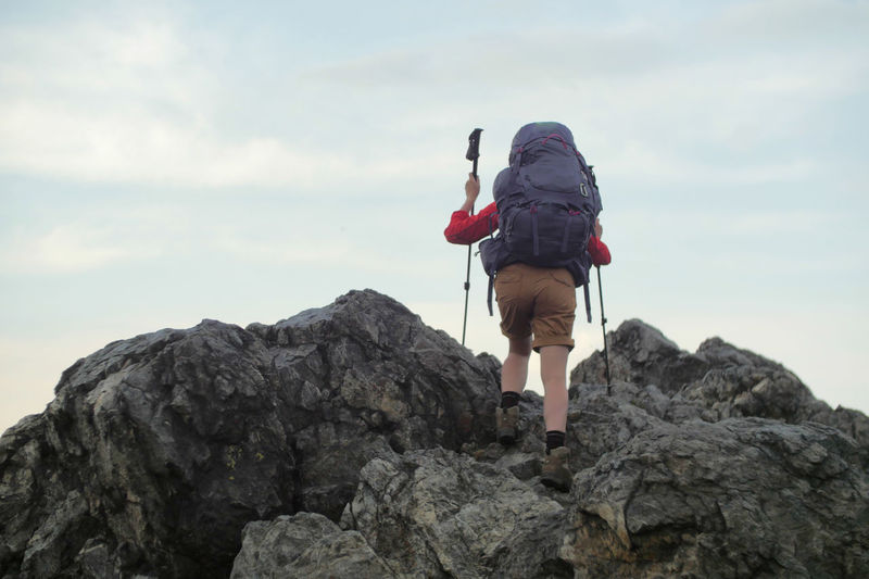 female hiker walking on a trail Alpine Backpacking Camping Expedition Freedom Hiking Nature Travel Trekking Woman Active Activity Adventure Backpack Boot Climbing Cloud - Sky Detail Female Full Length Hiking Hobbies Legs Leisure Activity Lifestyles Mountain Nature One Person Outdoors People person Real People Rear View Rock Rock - Object Rock Formation Sky Solid Trek Walking