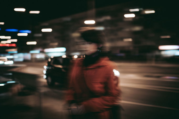 Rear view of man standing on road at night