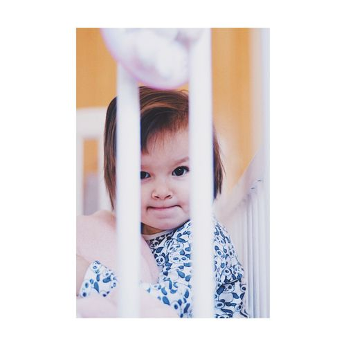 Portrait of cute baby girl in crib at home