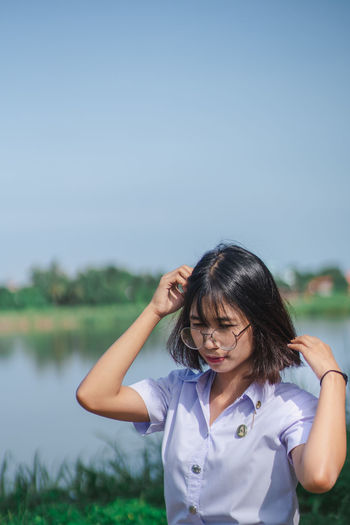 Woman standing by lake against clear blue sky