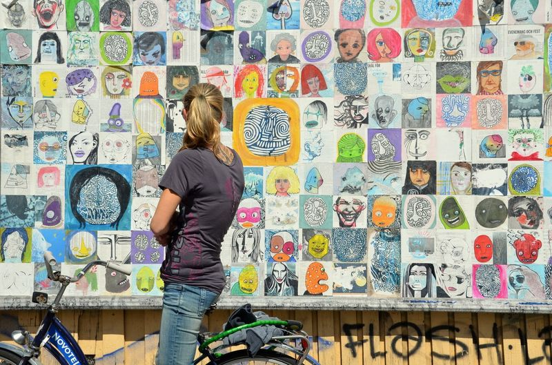 Young woman with bicycle looking at collage on wall