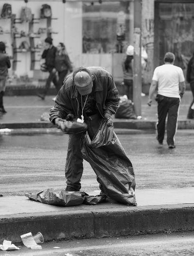 People on sidewalk in city inspecting trash bag