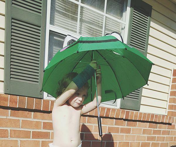 Shirtless Boy Holding Umbrella Against Building