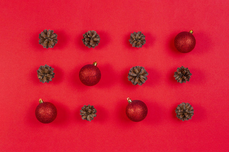 High Angle View Of Christmas Baubles And Pine Cones Against Red Background