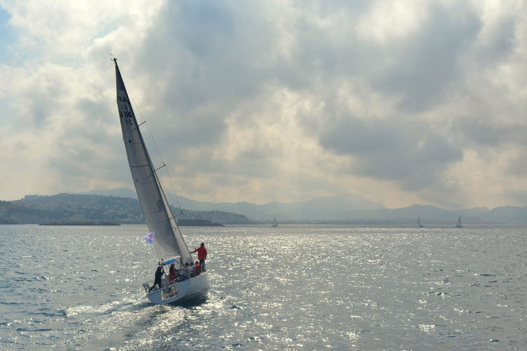 People on sailboat sailing in sea against sky