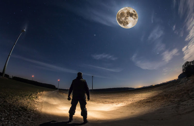 a man stands in a field at night and sees the full moon Sky Moon Astronomy Real People Rear View Night Space Men Nature Land Full Length Leisure Activity People Star - Space Full Moon Cloud - Sky Lifestyles Beauty In Nature Standing Outdoors Moonlight Brandenburg Germany Man Wind Turbines