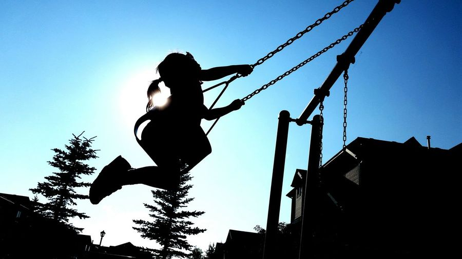 Low angle view of silhouette girl swinging against clear blue sky