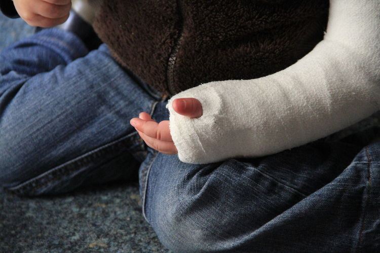 Midsection Of Child With Cast At Home