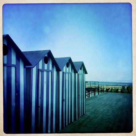 Beach hut against clear blue sky