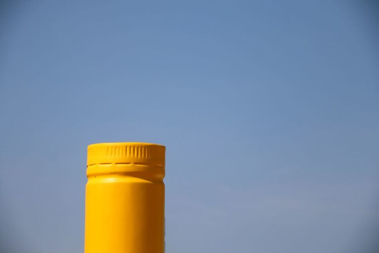 Low angle view of yellow bottle against blue sky