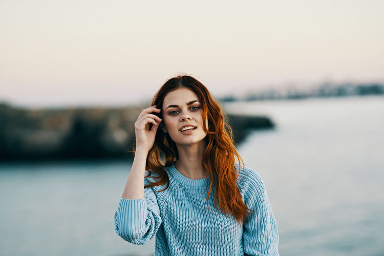 Portrait of smiling young woman standing on shore