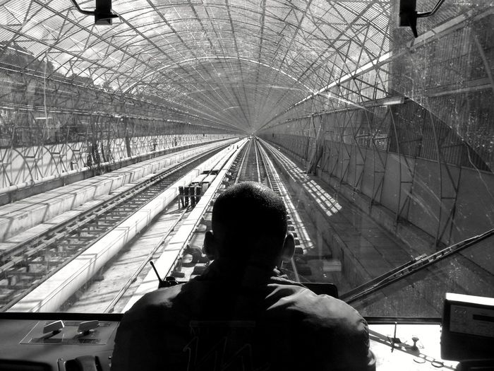 Rear view of woman on railroad tracks