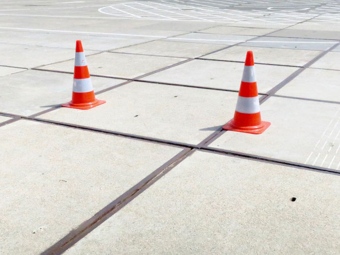 two pylons on a deserted parking lot in the harbor of Scheveningen Netherlands Parkinglot Pattern Pavement Scheveningen  Street Pylon Orange White LINE Cement Traffic Cone Cone No People Transportation Sign Security Outdoors Orange Color Guidance City Communication Day Road Shadow Rules