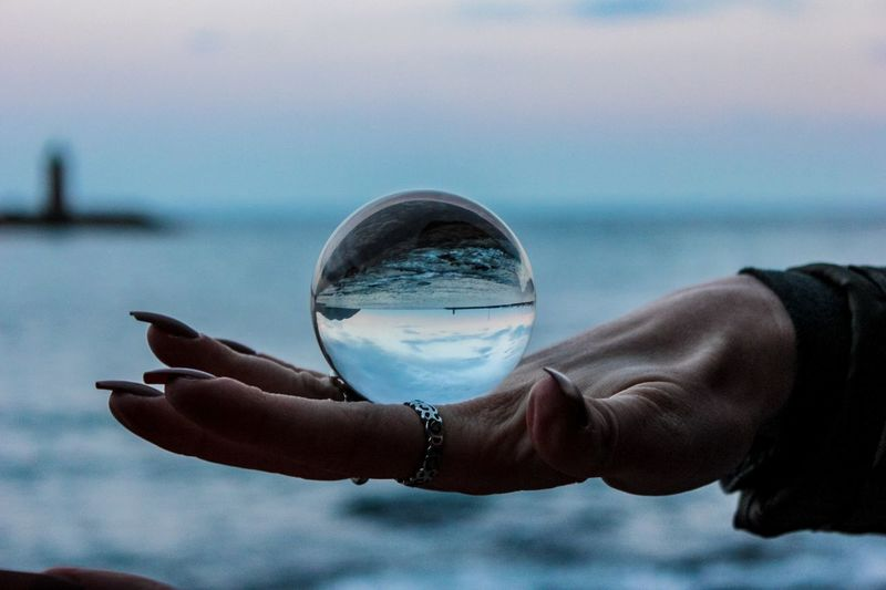 One Person Human Hand Water Human Body Part Hand Nature Summer Exploratorium Crystal Ball Sky Outdoors Sea Holding Focus On Foreground Day Close-up Reflection Real People Sphere Beauty In Nature Finger