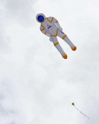 Low angle view of person flying against sky