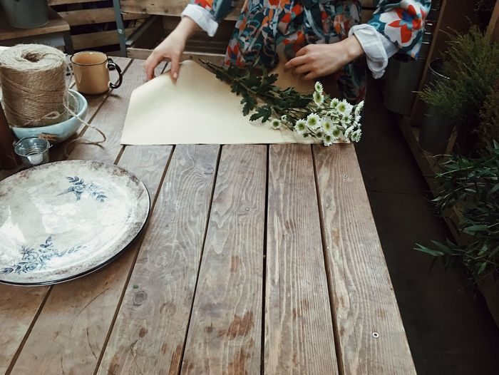 Midsection of woman wrapping flowers at table