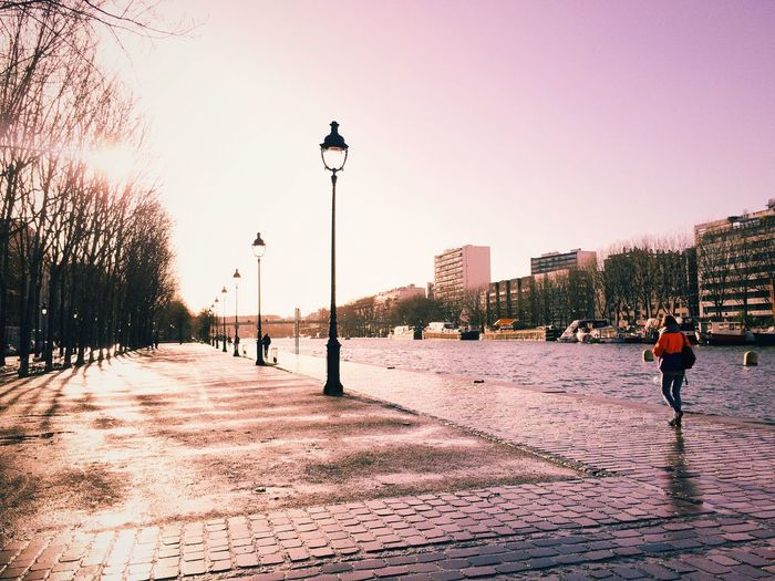 People walking on footpath against clear sky