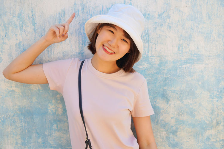 Portrait of smiling young woman standing against wall