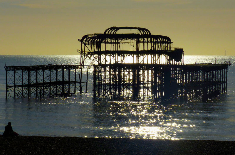 Silhouette pier on sea against sky at sunset