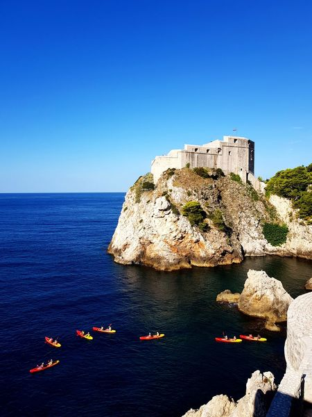 Kayaks & Fort Lovrijenac Kayak Fort Fortress EyeEm Selects Dubrovnik Croatia Adriatic Sea Water Clear Sky Sea Cliff Blue Rock - Object Beach Sky Horizon Over Water Paddling