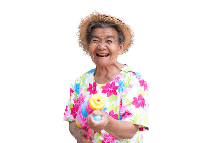 Portrait Of Smiling Senior Woman With Water Gun Standing Against White Background