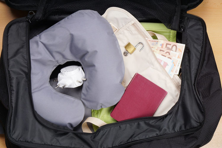 High angle view of padlock and neck pillow in suitcase