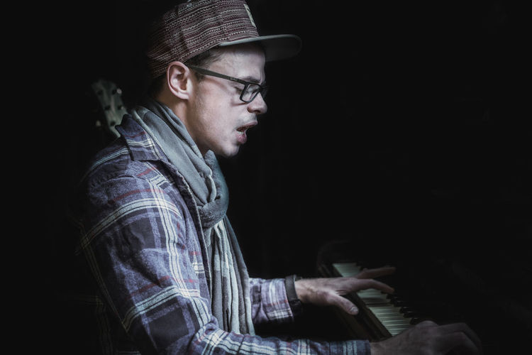 Music Young Adult Side View Clothing Musical Instrument Young Men One Person Indoors  Hat Musical Equipment Glasses Piano Black Background Arts Culture And Entertainment Eyeglasses  Looking Musician Checked Pattern Casual Clothing Profile View Contemplation Keyboard Exploring Fun