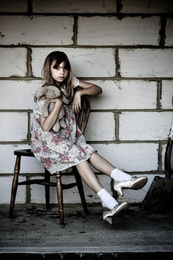 Portrait Of Girl Holding Stuffed Toy And Sitting On Chair Against Wall